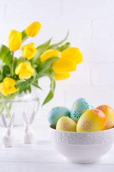 Bowl with colorful easter eggs, spring easter decoration on white wooden table with bouquet of yellow tulip flowers in glass vase on white background. easter interior decoration