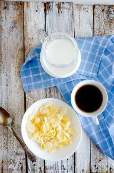 Чаша с кукурузными хлопьями в сахарной панировке и ложка, чашка кофе, молоко банка