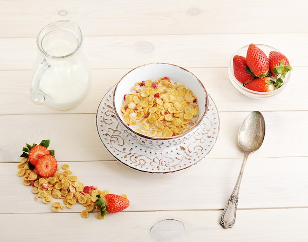 Bowl with corn flakes and strawberries with milk
