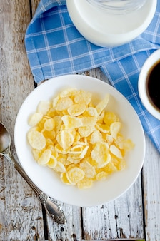 Bowl with corn flakes in sugarcoated and spoon, cup of coffee, jar milk on table