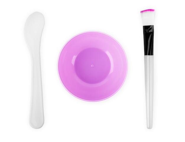 Чаша с косметической грязью, комплект для ухода за кожей га, кисть, ватные палочки на белом фоне