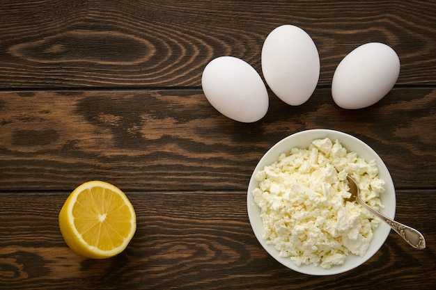 Bowl with cottage cheese, chicken eggs and lemon on a wooden table