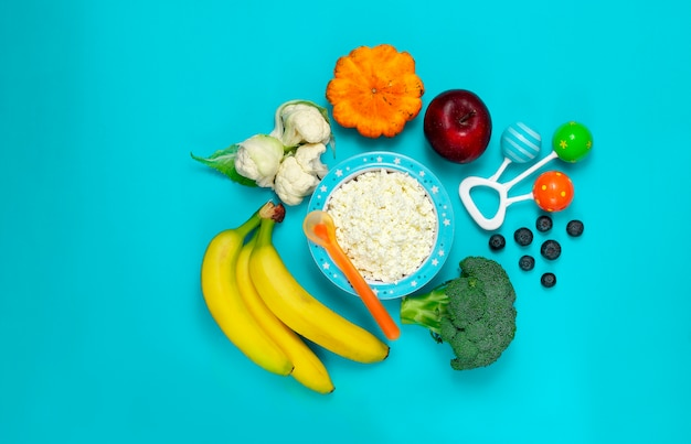 Bowl with cottage cheese, vegetables and fruits, baby food, rattle and spoon, on a blue background, top view, horizontal.