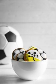 나무 테이블에 축구 스타일로 장식 된 창조적 인 쿠키와 그릇