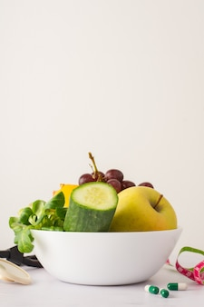 Bowl with cucumber and delicious apple on the table