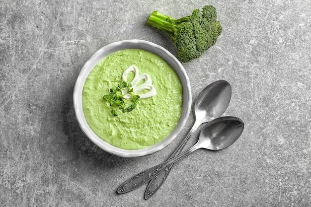 Bowl with delicious broccoli soup on grey table