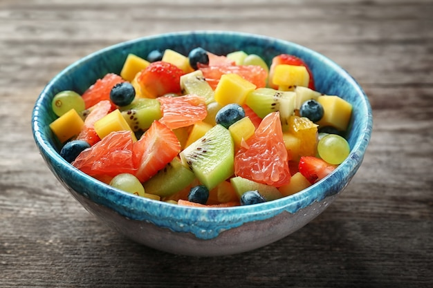 Чаша с вкусным фруктовым салатом на деревянном столе