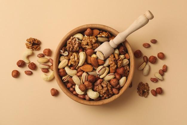 Чаша с разными орехами и деревянной ложкой на бежевом фоне