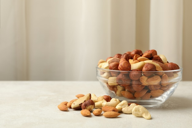 Bowl with different nuts on white textured table