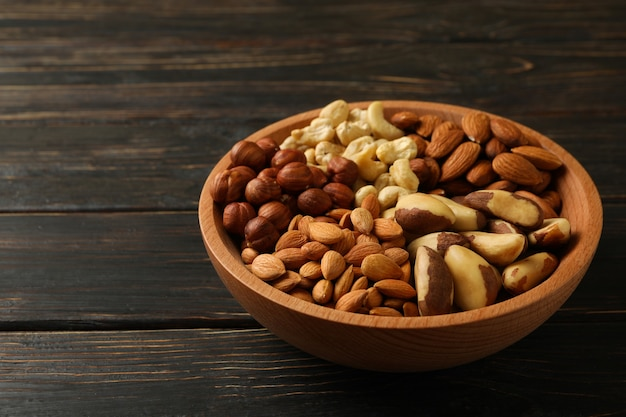 Bowl with different nuts on wooden table