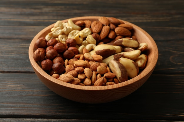 Bowl with different nuts on wooden