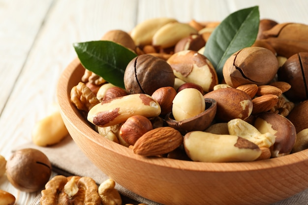 Bowl with different tasty nuts on white wooden table
