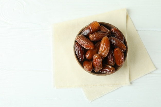Bowl with dried dates on kitchen napkin on white wooden table