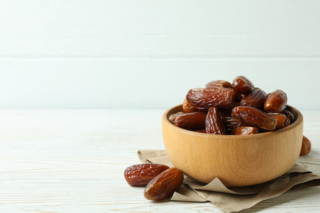 Bowl with dried dates on paper on white wooden table