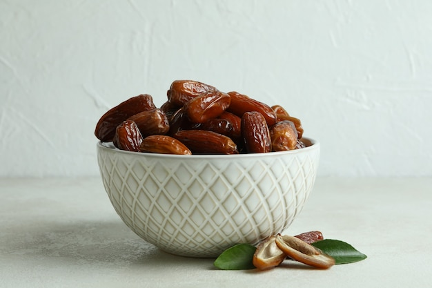 Bowl with dried dates on white textured table Premium Photo