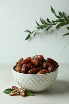 Bowl with dried dates on white textured table