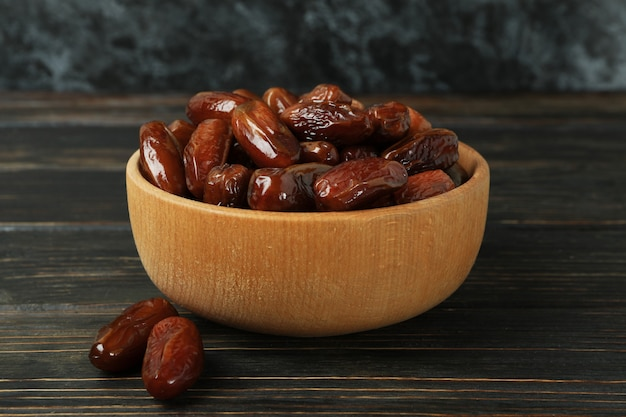 Bowl with dried dates on wooden table