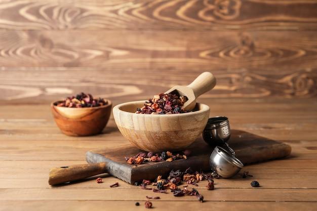 木製の背景にドライフルーツ茶とボウル