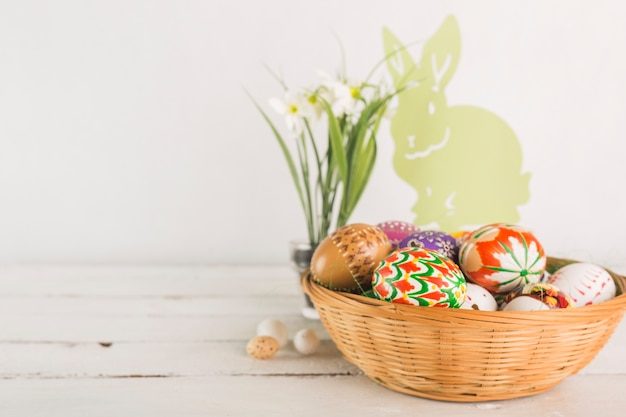 Bowl with easter eggs near decorations