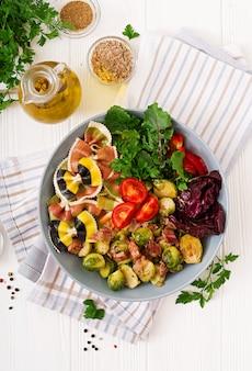 ファルファッレパスタ、ブリュッセルもやし、ベーコンと新鮮野菜のサラダ。フラット横たわっていた。上面図