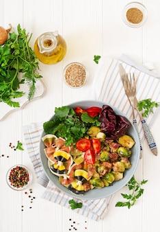 Ciotola con pasta farfalle, cavoletti di bruxelles con pancetta e insalata di verdure fresche. disteso. vista dall'alto