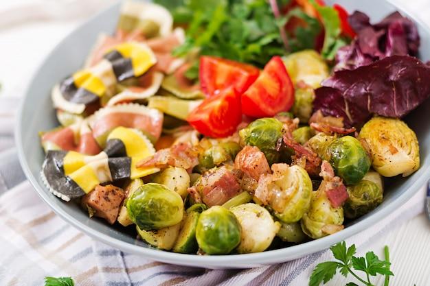 Ciotola con pasta farfalle, cavoletti di bruxelles con pancetta e insalata di verdure fresche