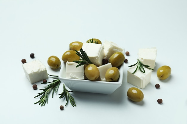 Bowl with feta, olives, rosemary and pepper on white