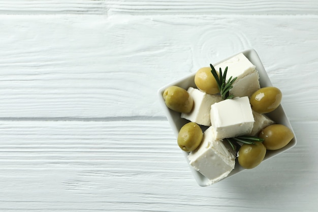 Bowl with feta, olives and rosemary on white wooden