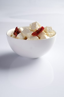 Bowl with feta pieces cheese and dried tomatoes with oil