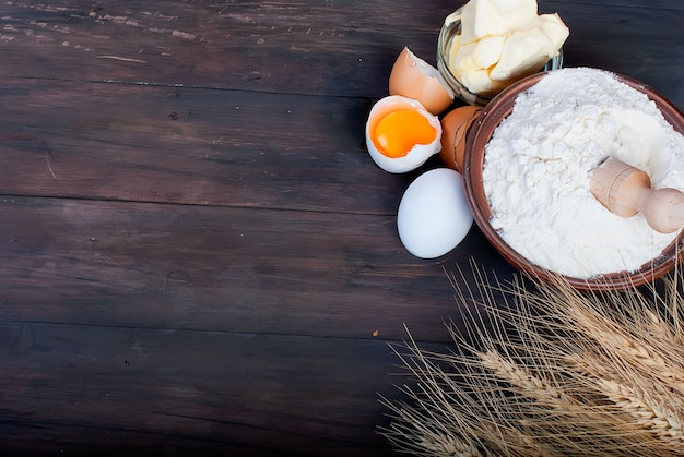 Bowl with flour eggs ears of wheat and butter on vintage wooden board food and drink concept