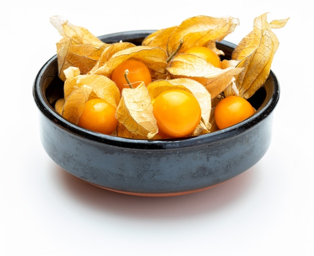 Bowl with flowers and fruits of fisalis (physalis peruviana) isolated