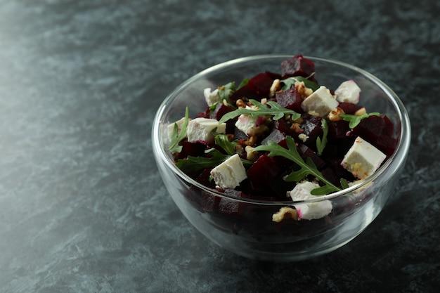 Bowl with fresh beet salad on black smoky table