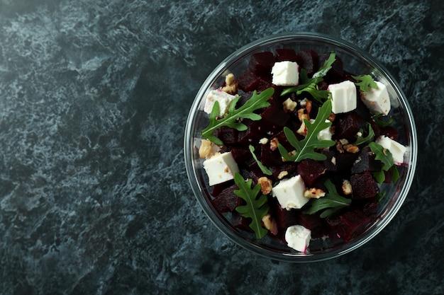 Bowl with fresh beet salad on black smoky