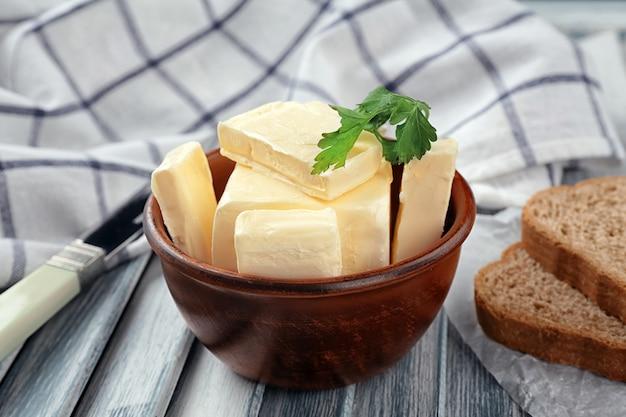 木製のテーブルに新鮮なバターとボウル