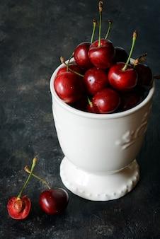 Чаша со свежей вишней на темном фоне