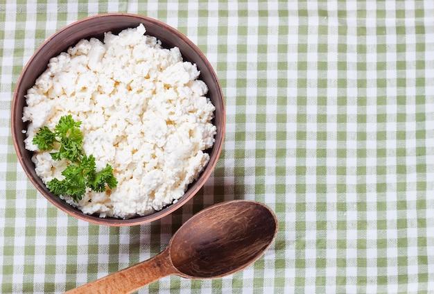 緑の市松模様のテーブルクロスの背景に新鮮なカッテージチーズと木のスプーンとボウル