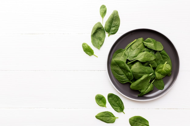 白い背景の上にほうれん草の新鮮な緑のサラダの葉とボウル。健康的な食事の概念