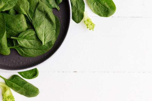 新鮮な緑のサラダの葉、ほうれん草、レタス、白い背景の上のバジルとボウル