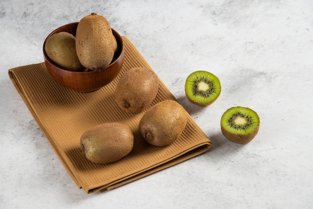 Bowl with fresh kiwi fruits on brown tablecloth