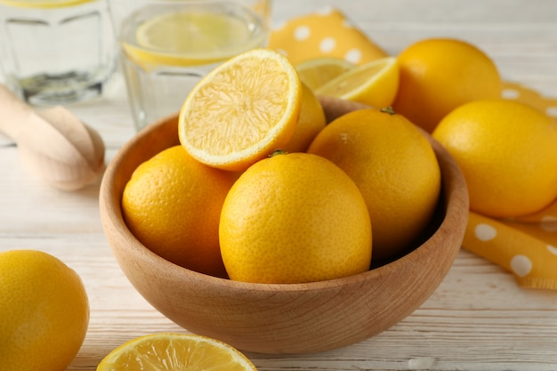 Bowl with fresh lemons on wooden table, close up