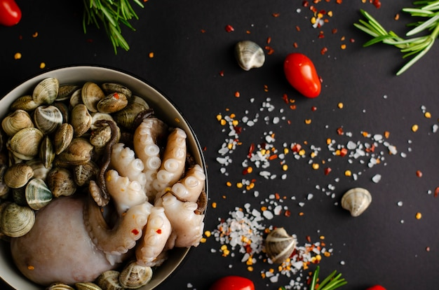 A bowl with fresh octopus with clams and ingredients for cooking on a black background