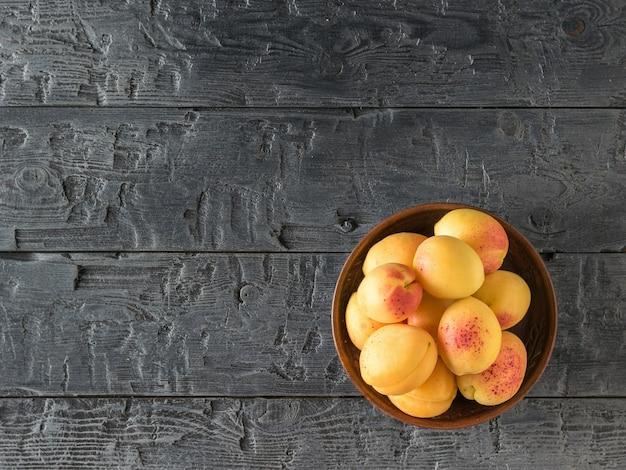 暗い木製のテーブルの上に新鮮な熟したアプリコットとボウル