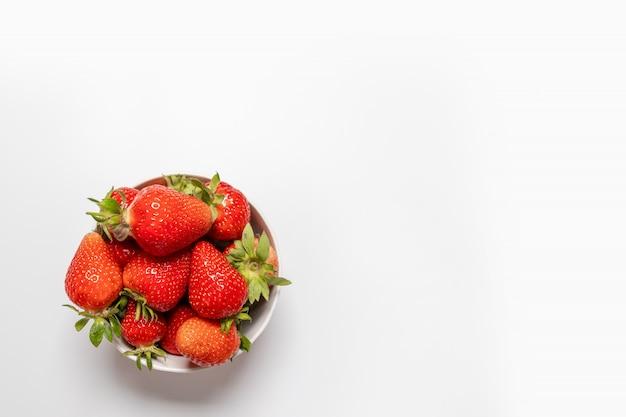 白い背景の上に新鮮なイチゴをボウルします。夏の構図、最小限のスタイル