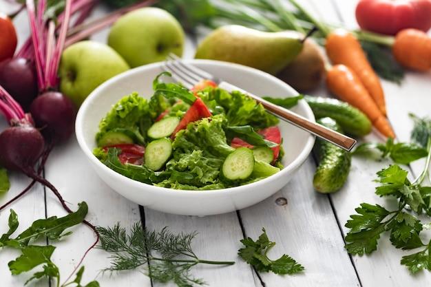 白い木製のテーブル、健康食品に新鮮な夏のサラダと食材を入れたボウル