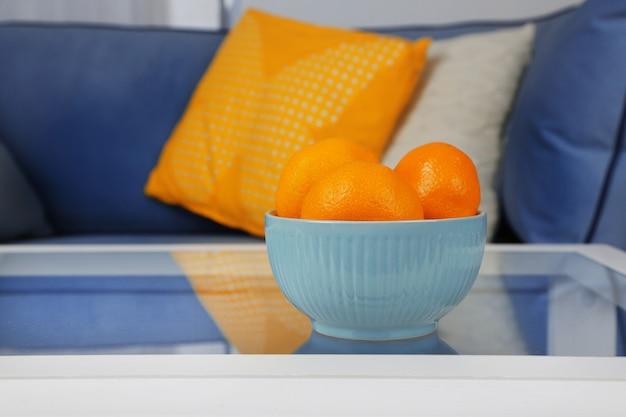 Чаша со свежими мандаринами на столе в гостиной, крупным планом