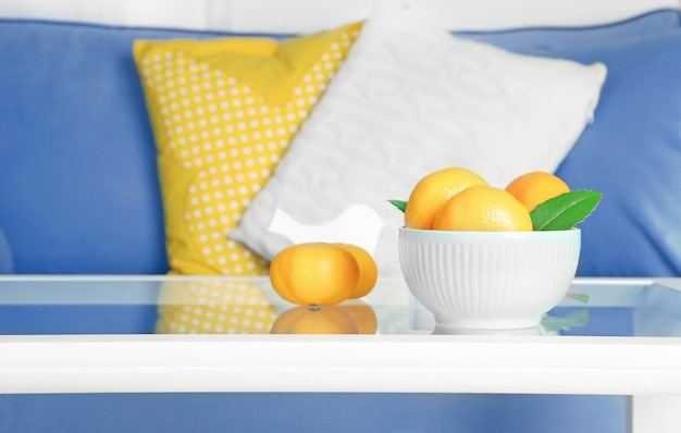 Bowl with fresh tangerines on table in living room