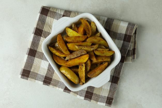Bowl with fried potato on kitchen towel, on white textured