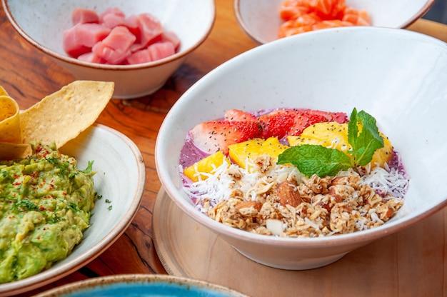 하얀 접시에 과일과 그래놀라를 넣은 그릇