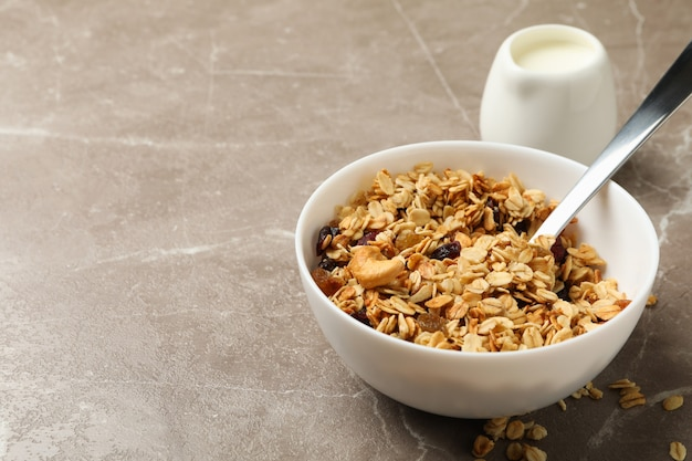 Bowl with granola and milk on gray background