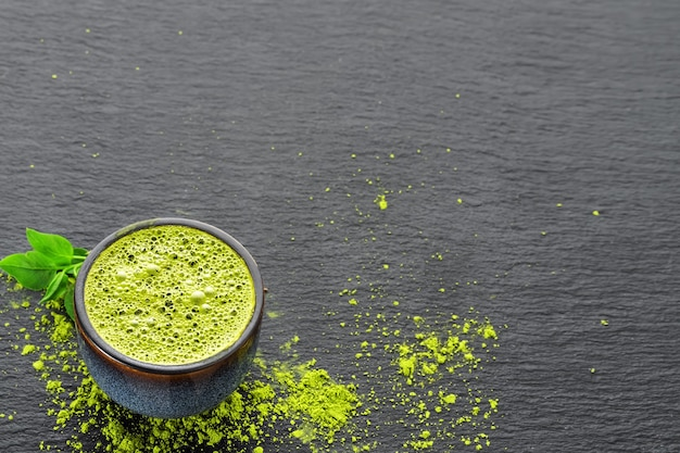 Bowl with green tea matcha, next to tea leaves and tea powder on a black stone table